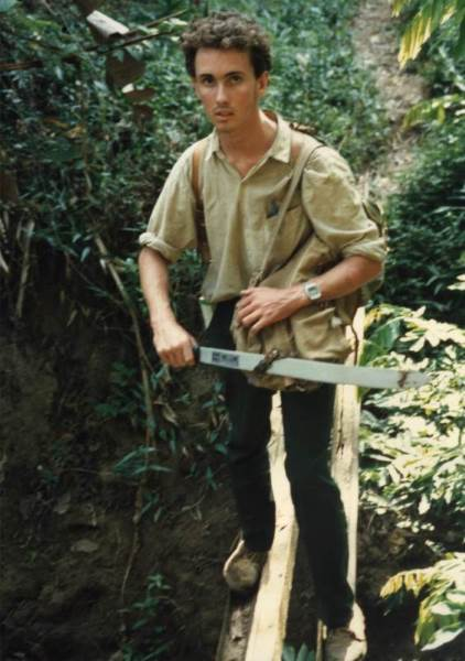 The author (Andrew Egan) crossing a log bridge               on day one of the expedition with a newly-purchased               machete